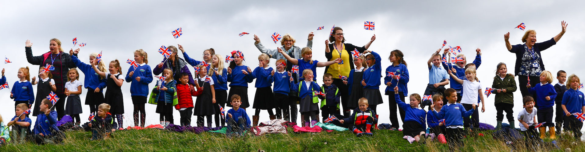 A group of spectators wave flags to support cyclists during the Tour of Britain.