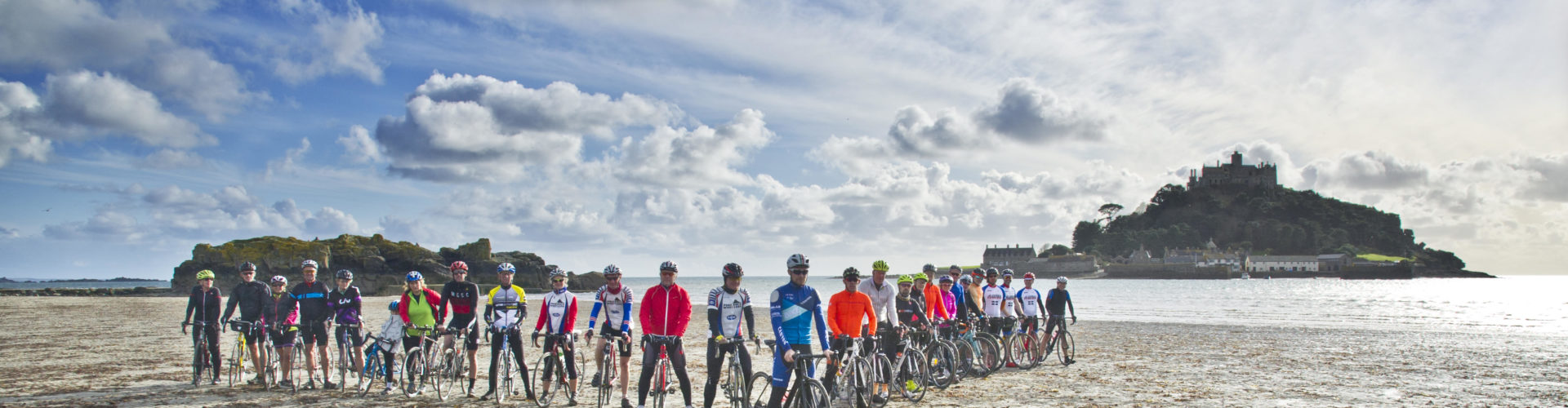 Cyclists stand in front of St Michael's Mount at Marazion